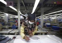 Pekerja sedang mengukur bahan untuk dibuat menjadi pakaian di salah satu pabrik di Tangerang, Banten, Senin (11/2/2019).