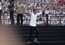 Capres nomor urut 01 Joko Widodo berlari menuju panggung saat menghadiri Konser Putih Bersatu di Stadion Utama Gelora Bung Karno, Senayan, Jakarta