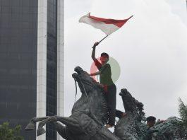 Seorang pelajar memasang bendera merah putih di patung kuda Jakarta, Selasa (20/10/2020)